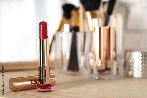 Canvastavla  Bright lipstick in gold tube on dressing table, space for text