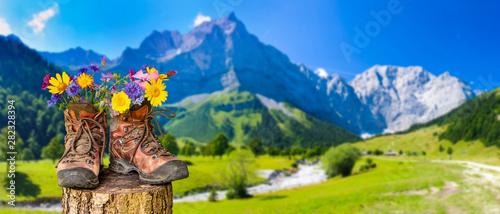 Obraz Wanderschuhe mit Blumen in schöner bayerischer Landschaft - fototapety do salonu