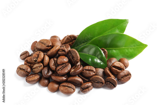 Roasted coffee beans and fresh green leaves on white background Canvas Print