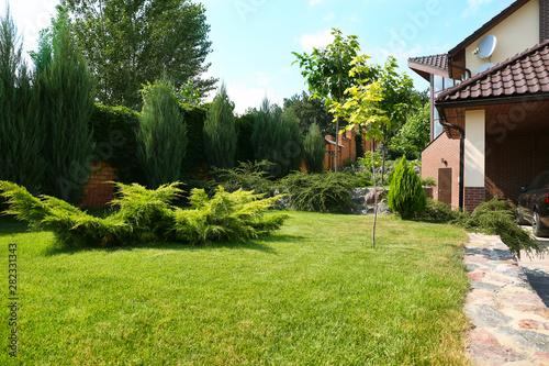 Obraz Landscape with modern house and beautiful garden on sunny day - fototapety do salonu