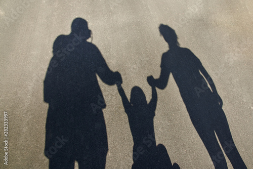 Silhouette of a family on the pavement: dad, mom and baby holding hands Tablou Canvas