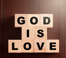God Is Love Spelled In Blocks On A Brown Leather Holy Bible