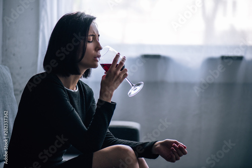 depressed lonely woman sitting on couch and drinking wine at home Wallpaper Mural