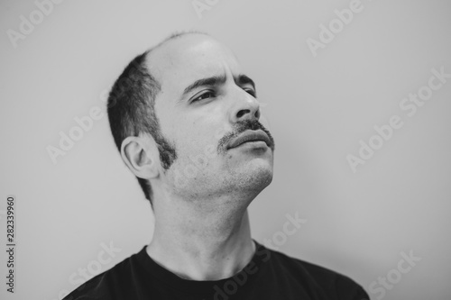 Photo  White man with a prominent mustache looking into the distance against a seamless