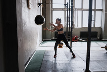 Woman Doing Exercise With Heavy Medicine Ball In Gym.