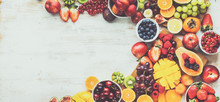 Healthy Raw Fruits Background, Cut Mango Papaya, Strawberries Raspberries Oranges Plums Apples Kiwis Grapes Blueberries Cherries, On White Table, Copy Space, Top View, Toned, Banner, Selective Focus