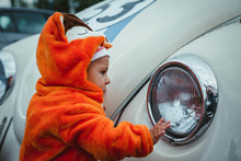 A Small Child In A Fox Costume Stands Near A Restored Old Car And Examines It With Interest. Baby In Kigurumi Or Pajamas
