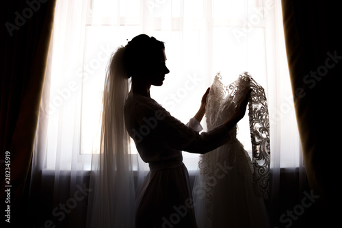 Fotografia  Bride holding white wedding dress with lace, embroidery