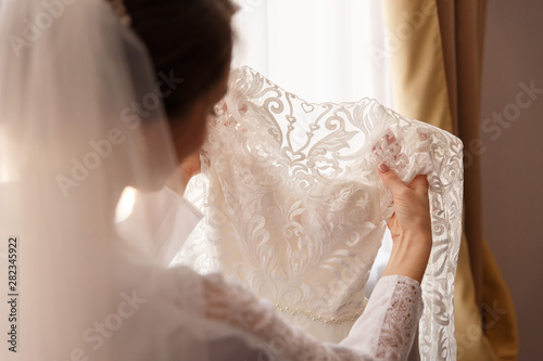 Pinturas sobre lienzo  Bride holding white wedding dress with lace, embroidery