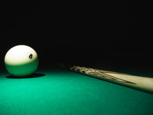White Ball Number 8 From Russian Billiard Pyramid And A Cue On A Table. Black Background