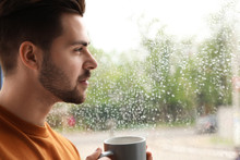 Thoughtful Handsome Man With Cup Of Coffee Near Window Indoors On Rainy Day