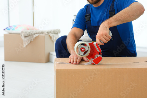 Fototapeta Young worker packing box in room, closeup. Moving service obraz