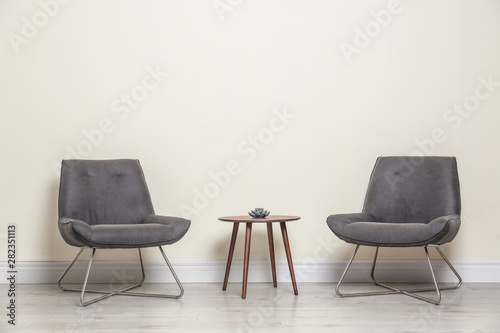 Room interior with modern chairs and table near light wall Canvas Print