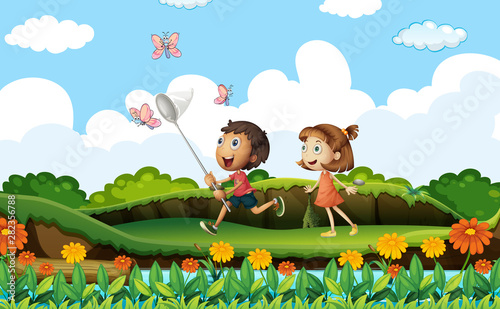 Two kids catching butterflies in the park