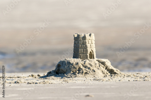 Foto Detailed sand castle on the beach with a tidal pool in the background