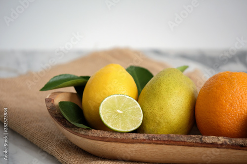 Fresh Common Citrus Fruits on wood plate on white marble table background - Image