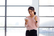 Young Asian Girl Looking At Her Mobile Phone And Get Excited Inside The Building. One Beautiful Woman Is Happy Watching At Smartphone Indoors.