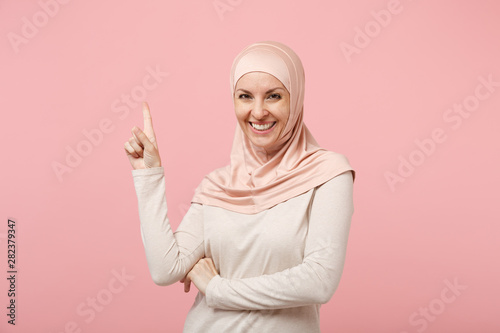 Fotografía  Smiling young arabian muslim woman in hijab light clothes posing isolated on pink wall background in studio