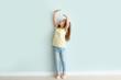Leinwandbild Motiv Cute little girl measuring her height near wall