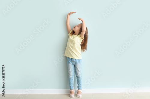 Obraz Cute little girl measuring her height near wall - fototapety do salonu