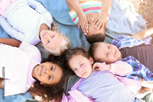 Fototapeta Group of happy children lying on plaid outdoors, top view obraz na płótnie