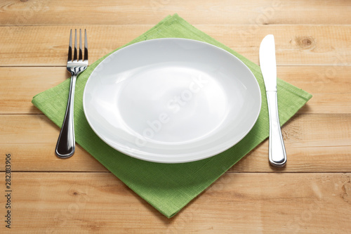 plate, knife and fork at rustic wooden background Canvas Print