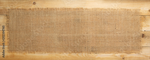 Fotografering  burlap hessian sacking on wooden background