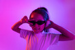 Leinwanddruck Bild - Beautiful female half-length portrait isolated on purple backgroud in neon light. Young emotional teen girl in sunglasses. Human emotions, facial expression concept. Trendy colors. Dancing, smiling.