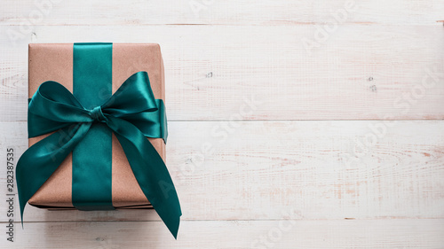 Fotografía  Gift box in craft wrapping paper and green satin ribbon on white wooden table, copy space right