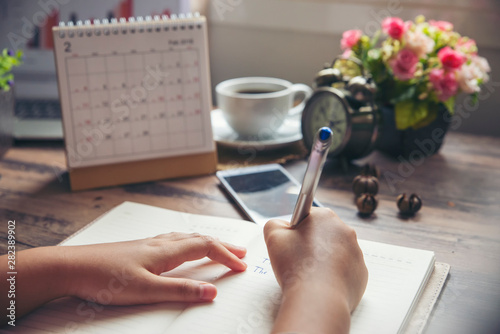 Obraz Work online at home, On Diary book, Man's hand planner or organizer writing daily appointment, mark and noted schedule (meeting) on book or diary at office desk. Planner concept. - fototapety do salonu