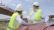Male and female engineers are discussing a flyover construction project. Developers are working on project documentation at a construction site.
