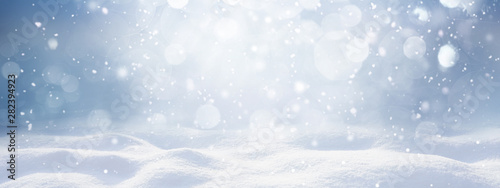 Winter snow background with snowdrifts, with beautiful light and snow flakes on the blue sky, beautiful bokeh circles, banner format, copy space.