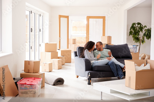 Couple Taking A Break And Sitting On Sofa Celebrating Moving Into New Home With Champagne