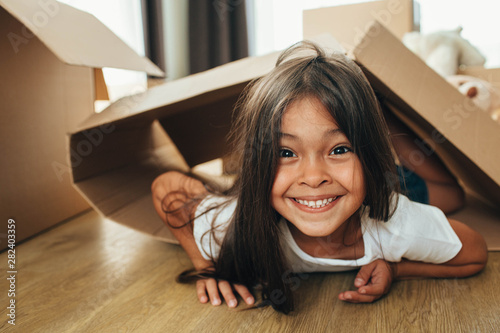 Photo Happy mixed race little girl playing with cardboard boxes, having fun while movi