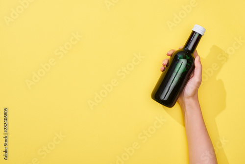 Poster de jardin Fleur cropped view of woman holding glass bottle on yellow background