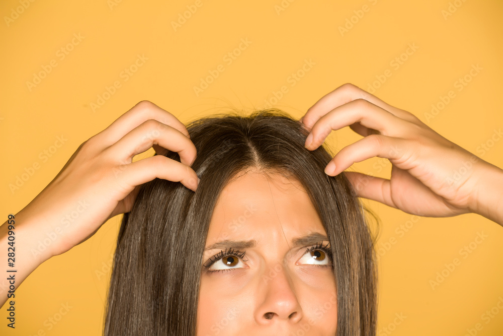 Fototapeta Beautiful young woman with itchy scalp on yellow background