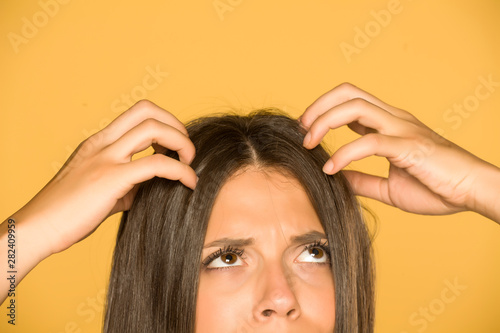 Fotografia Beautiful young woman with itchy scalp on yellow background