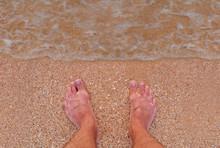 Men's Feet Stand On A Sandy Beach. Surf