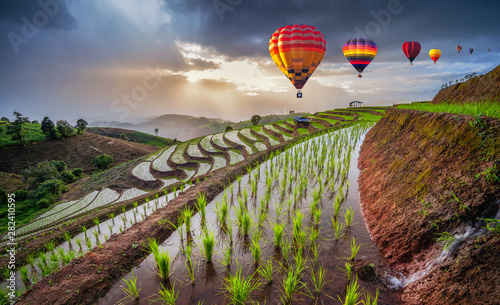 Fotobehang Rijstvelden Colorful hot air balloons flying above Terraced Paddy Field in Mae-Jam Village on sunset time in Ban Pa Bong Piang, Chaing Mai Province , Thailand, Asia..