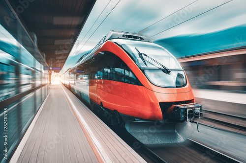 High speed orange train in motion on the railway station at sunset. Modern intercity passenger train with motion blur effect on the railway platform. Industrial. Railroad in Europe. Transport