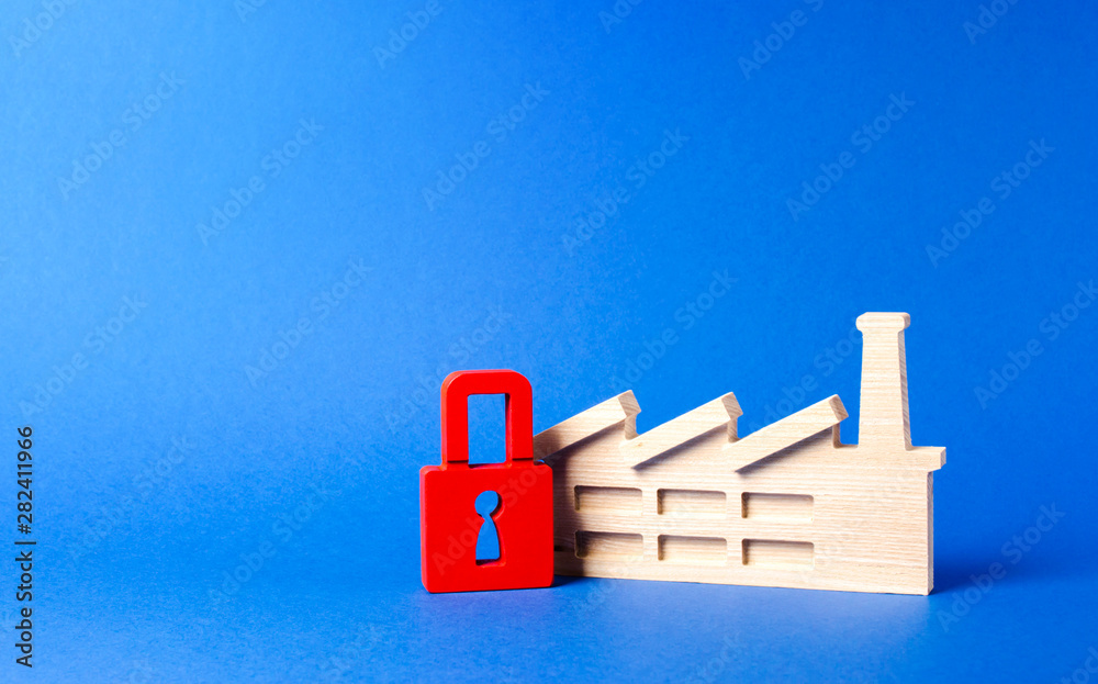 Factory figurine and red padlock. closure of harmful production. Freezing of assets, bankrupt. Law prohibition and sanctions against industrial facilities and factories. Business support and subsidies