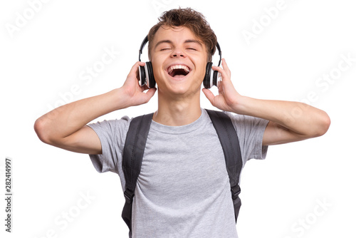 Happy teen boy with headphones and backpack, isolated on white background. Cheerful child listening to music and singing song. Emotional portrait of handsome teenager enjoying music Back to school. - 282414997