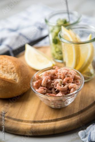 Fototapeta Norddeutsche Friesische Nordseekrabben in Glas Schale mit Brötchen, Gurkensalat und Zitronen auf Holz Brett obraz
