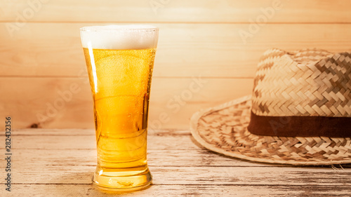Lager beer in a tall glass Placed on a rustic wooden floor with a weaving hat Canvas Print