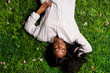 canvas print picture - Portrait of beautiful african american woman laying on green grass in park