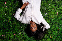 Portrait Of Beautiful African American Woman Laying On Green Grass In Park
