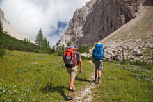Some Hikers Walk Along A Mountain Path.