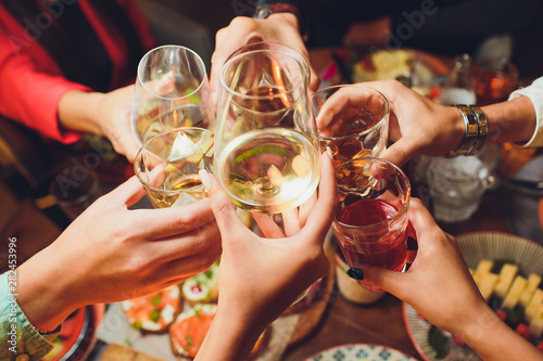 Photo Human hands with glasses of red wine clinking them over served table