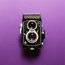 Aachen/Germany - May 11, 2019. The Old Japan Medium Format Film TLR Camera Yashica Copal MX, Displayed On A Purple Background.
