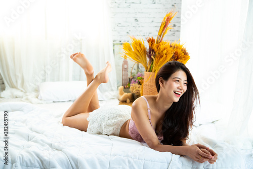 Beautiful young girl in a sexy wearing sexy luxury stylish pink lingerie lying on the bed